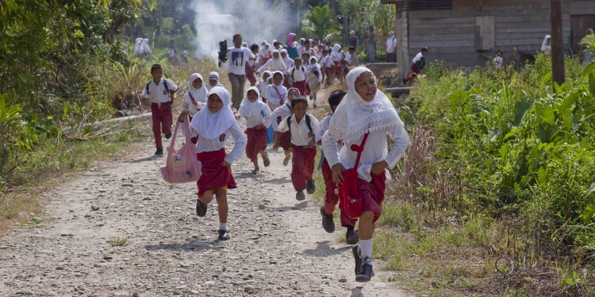 Niñas y niños corren durante el simulacro de una evacuación de emergencia organizada por el equipo de Preparación para Desastres del JRS en la aldea de Lawe Sawah.